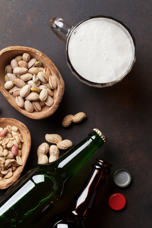 Lager beer and snacks on stone table. Various nuts. Top view Stock Photo