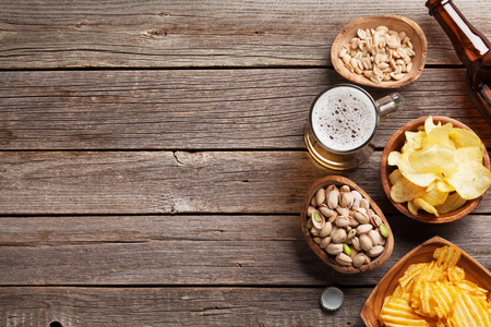 Lager beer mug and snacks on a wooden table. Nuts, chips. Top view with copy space