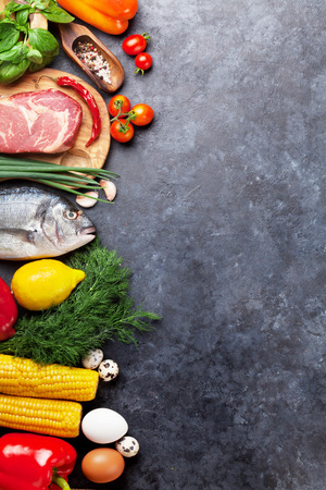 野菜、魚、肉、調理用の材料。トマト、コショウ、トウモロコシ、牛肉、卵。石造りのテーブルのコピースペースが付いている上の眺め