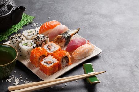 石造りのテーブルに寿司、マキ、緑茶のセット。コピースペースを使用したビュー