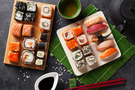 Set of sushi and maki roll and green tea on stone table. Top view Stock Photo