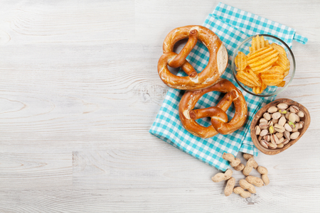 Beer snacks on wooden table. Nuts, chips, pretzel. Top view with copy space Stock Photo