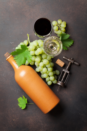 Wine glasses, bottle and grapes on stone table. Top view Stock Photo