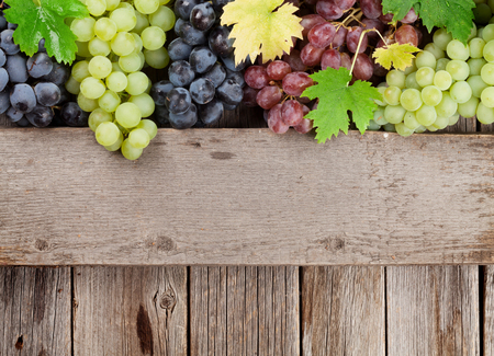 Various colorful grapes on wooden background. With space for your text Stockfoto