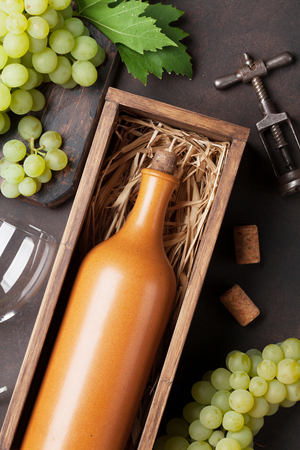 Wine bottle and grapes on stone table. Top view