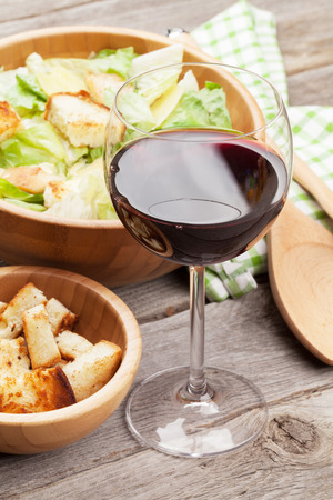 Red wine glass and caesar salad on wooden table
