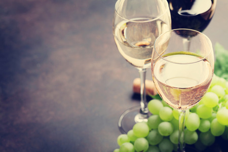 Wine glasses and grapes on stone table. With space for your text. Toned Stock Photo