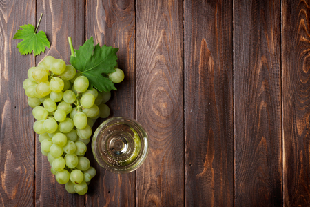 Wine glass and grapes on wooden table. Top view with copy space Stock Photo