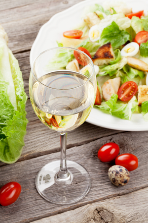 Fresh healthy salad and white wine on wooden table Imagens