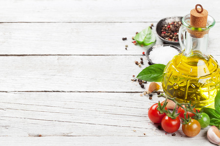 Tomatoes, basil and spices on wooden table. Cooking concept. With space for your text