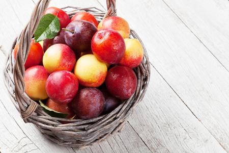 新鮮な熟した桃と木製のテーブル上のバスケットの梅。テキストのスペースで 写真素材