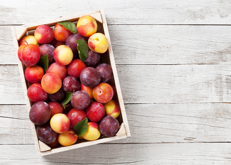 Fresh ripe peaches and plums in box on wooden table. Top view with space for your text