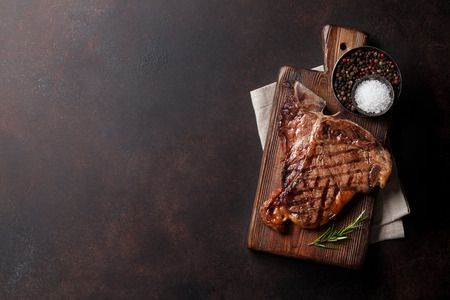 Grilled T-bone steak on stone table. Top view with copy space Stock Photo