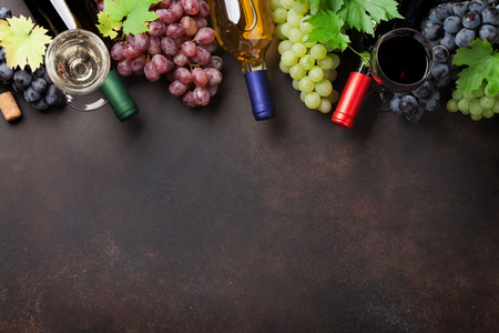 Wine bottles and grapes on stone table. Top view with space for your text