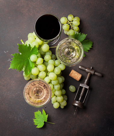 Wine glasses and grapes on stone table. Top view Stock Photo