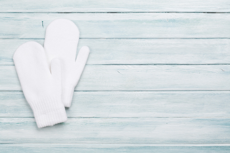 White mittens on wooden table. Christmas background. Top view with copy space