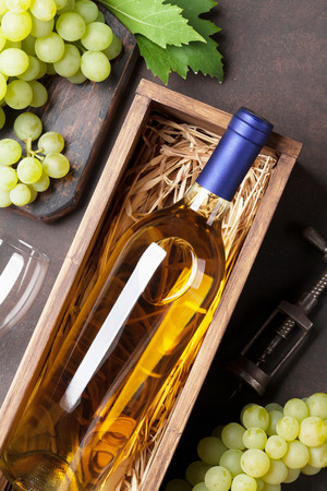 White wine bottle in box and grapes on stone table. Top view