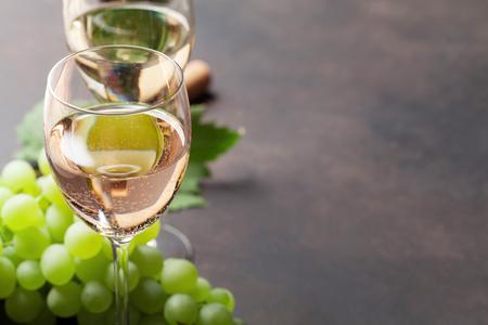 ワイングラスと石のテーブルの上のブドウ。テキストのスペースで
