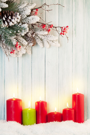 Christmas background with candles and snow fir tree in front of wooden wall with copy space