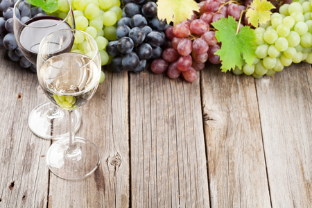 Wine glasses and grapes on wooden table. With space for your text