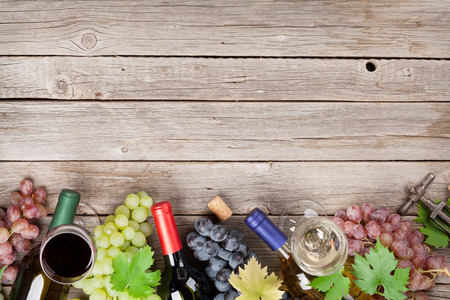 Wine bottles and grapes on wooden table. Top view with space for your text Stock fotó