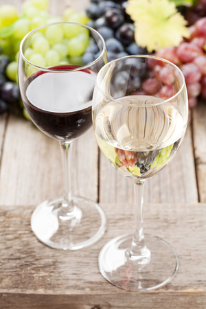 Wine glasses and grapes on wooden table