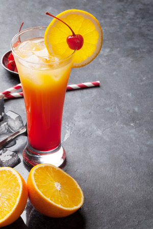 Tequila sunrise cocktail on dark stone table. With space for your text
