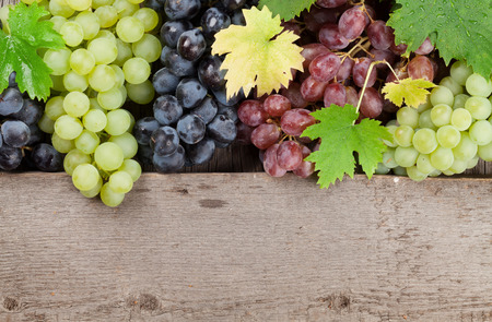 Varie uve colorate su fondo di legno con spazio per il testo Archivio Fotografico - 87592357