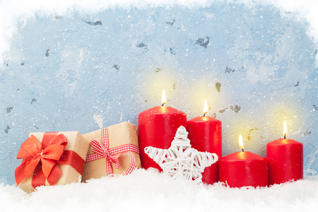Christmas background with candles and gift boxes in front of stone wall with copy space