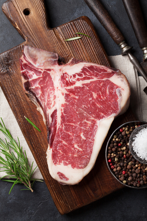 Raw T-bone steak cooking on stone table. Top view Stock fotó - 87835205
