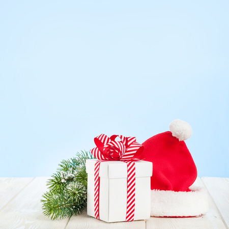 Christmas gift box, santa hat and fir tree branch on wooden table with background for copy space