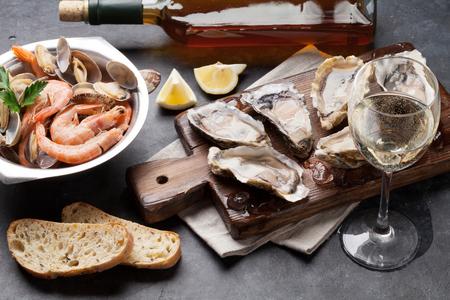 Verse zeevruchten en witte wijn op stenen tafel