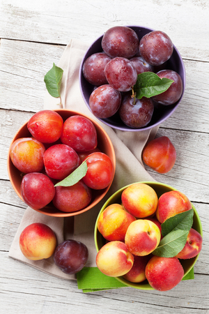 Fresh ripe peaches and plums on wooden table. Top view