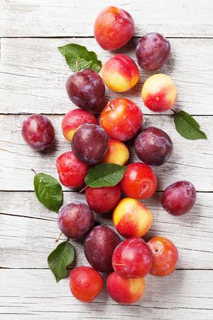 木製のテーブルの上に新鮮な熟した桃と梅。トップビュー