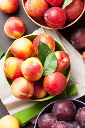 Fresh ripe peaches and plums on stone table. Top view