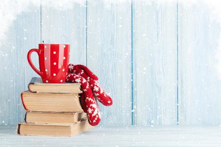 핫 초콜릿 컵과 책 위로 장갑입니다. 크리스마스. 사본 공간으로보기 스톡 콘텐츠