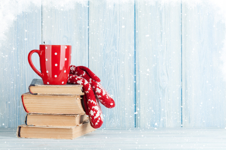 Hot chocolate cup and mittens over books. Christmas. View with copy space Foto de archivo