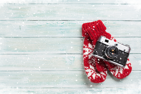 Xmas greeting card. Christmas background with camera and mittens. View from above with space for your greetings or photo
