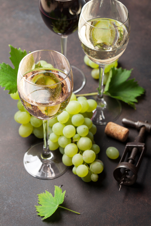 Wine glasses and grapes on stone table