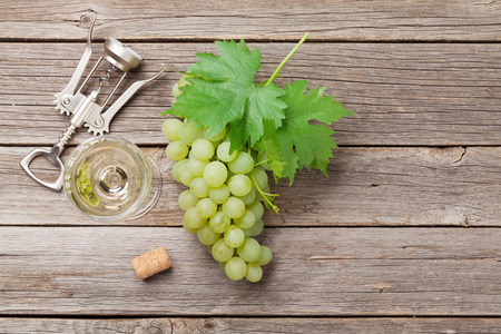 Wine glass and grapes on wooden table. Top view with space for your text