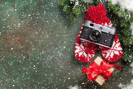 Cartão de Natal. Fundo do Natal com a árvore de abeto da neve, a câmera e a caixa de presente. Vista de cima com espaço para suas saudações ou foto Foto de archivo - 88289797