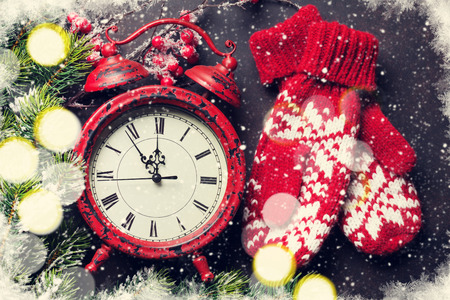 Xmas greeting card. Christmas background with snow fir tree, mittens and alarm clock. View from above. Toned Stok Fotoğraf
