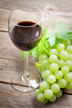 Wine glass and grapes on wooden table