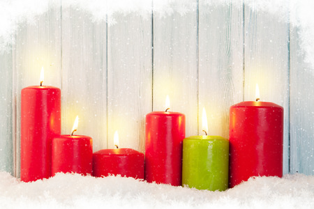 Christmas background with candles in snow in front of wooden wall with copy space