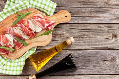 hams: Prosciutto and mozzarella on wooden table. Top view with copy space Foto de archivo
