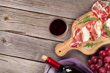 Prosciutto and mozzarella with red wine on wooden table. Top view with copy space Stock fotó