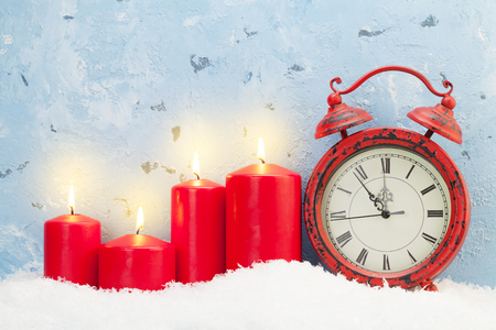 Christmas candles and alarm clock in snow in front of stone wall with copy space