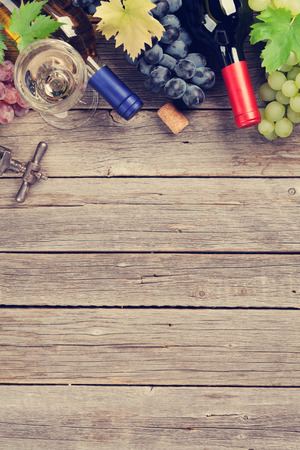 Wine bottles and grapes on wooden table. Top view with space for your text. Toned