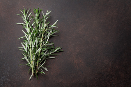 Rosemary herbs on dark stone table. Top view with space for your recipe