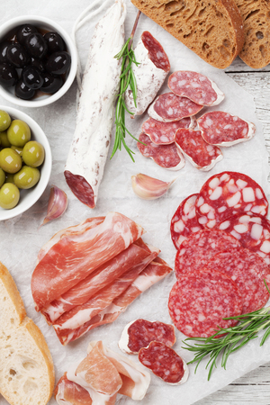 Salami, sliced ham, sausage, prosciutto, bacon, toasts, olives. Meat antipasto platter on wooden table. Top view Stock Photo